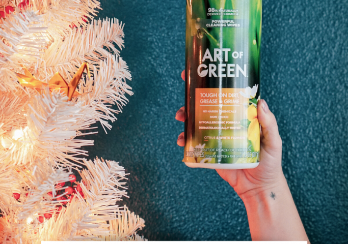 woman holding art of green cleaning wipes next to retro peach christmas tree