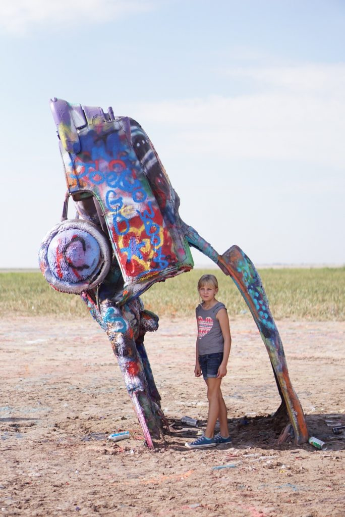 young girl standing in opening of car at cadillac ranch amarillo