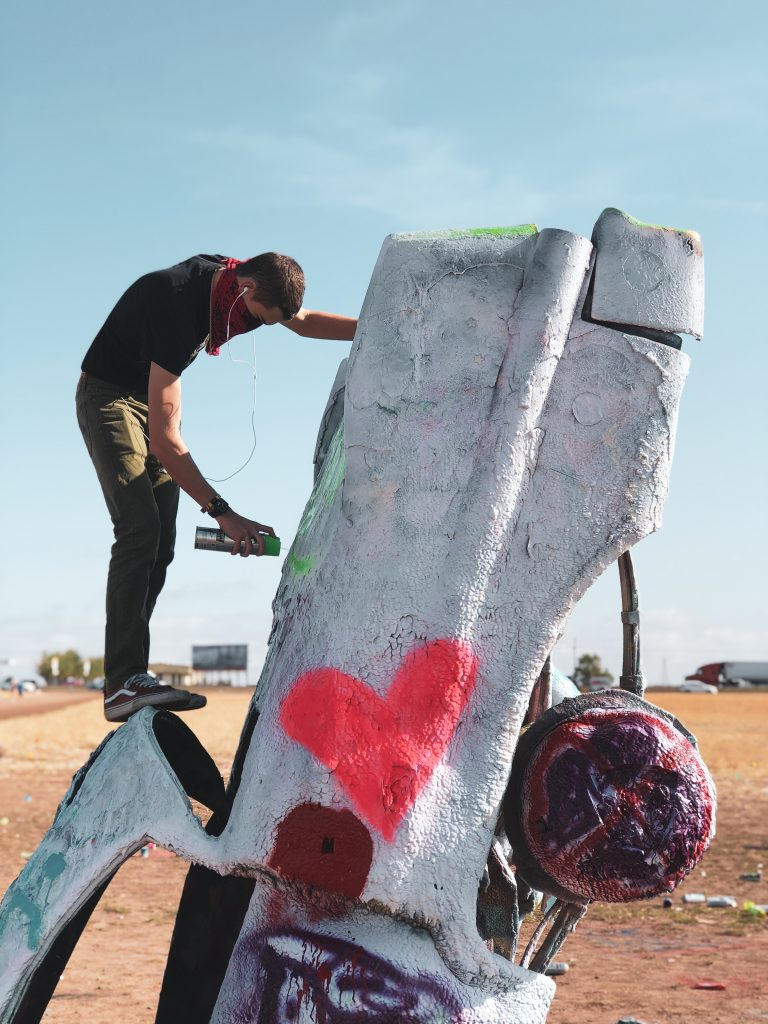 teen boy standing on white car and spray painting at cadillac ranch in amarillo