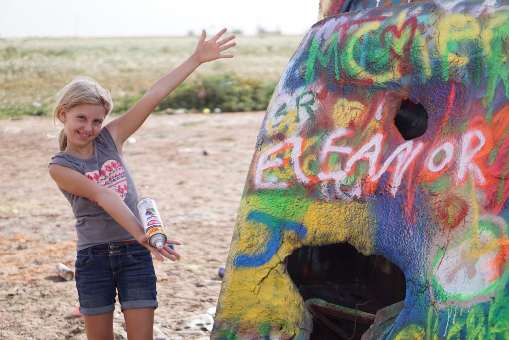 young girl showing off her spray paint on car at cadillac ranch amarillo