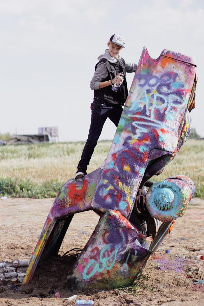 teen boy standing on car with spray paint at cadillac ranch amarillo