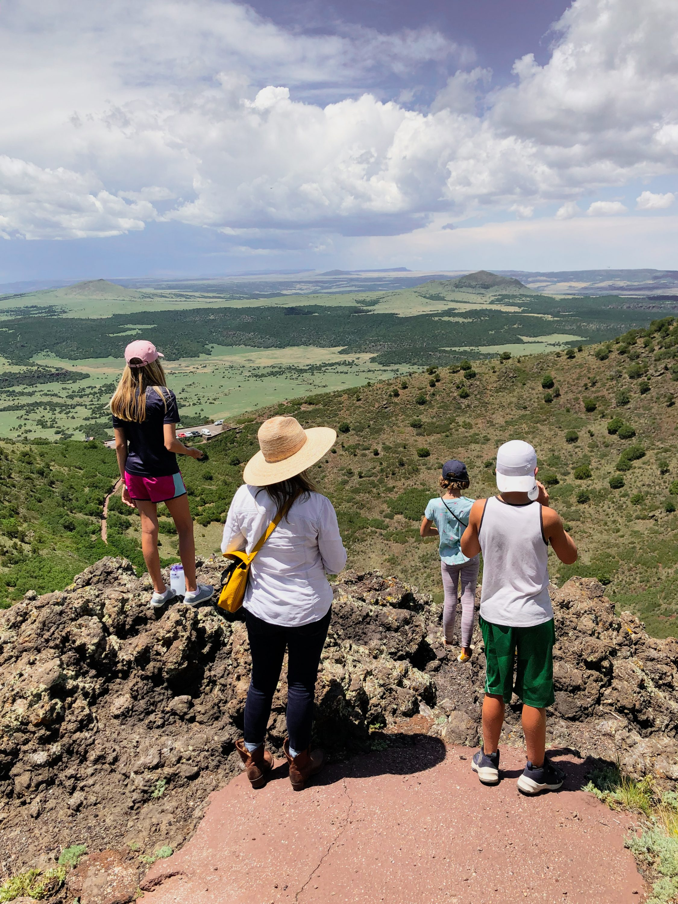 family standing at top of capulin volcano national monument and looking off at landscape