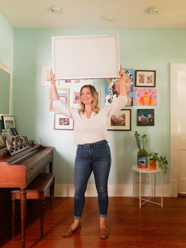 woman holding clean air filter over head